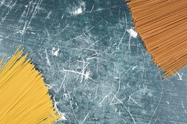 Nieprzygotowany pęczek makaronu spaghetti z pełnego ziarna na tle marmuru