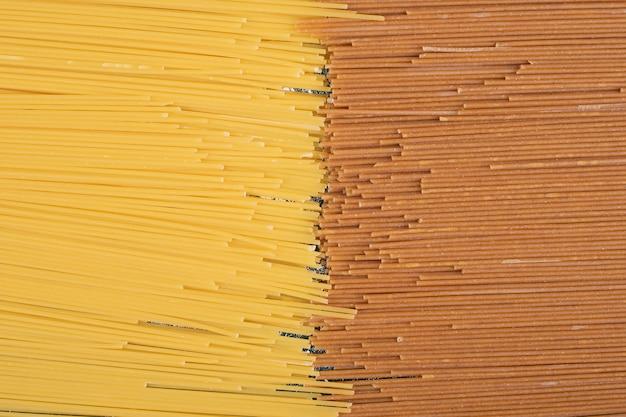 Nieprzygotowany świeży makaron brązowy i żółty na marmurowym tle. wysokiej jakości zdjęcie