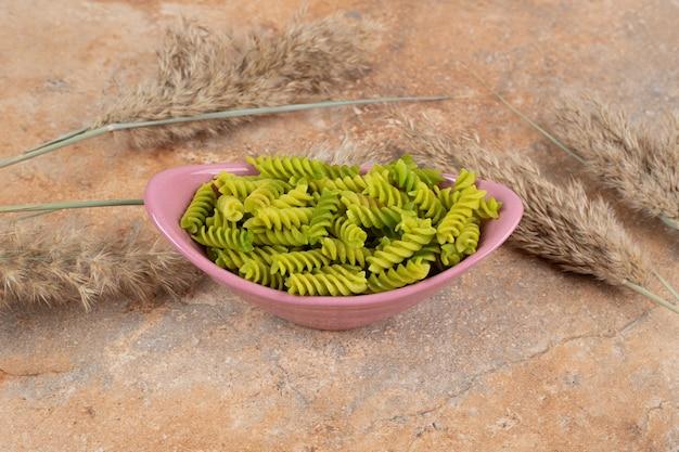 Nieprzygotowany zielony makaron spirali na różowej misce. wysokiej jakości zdjęcie