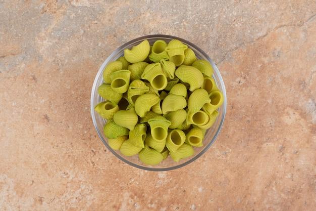 Nieprzygotowany zielony makaron w szklanej płytce na marmurowym tle. wysokiej jakości zdjęcie