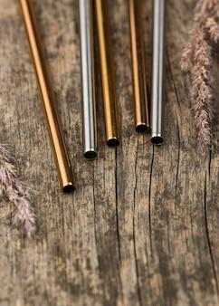 Nierdzewne metalowe słomki na drewnianym tle