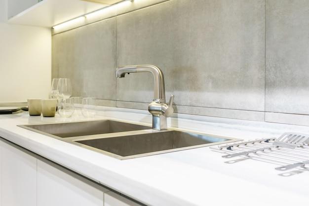 Nierdzewny zlew kuchenny i woda z kranu w kuchni. wbudowane urządzenia. urządzenie kuchenne