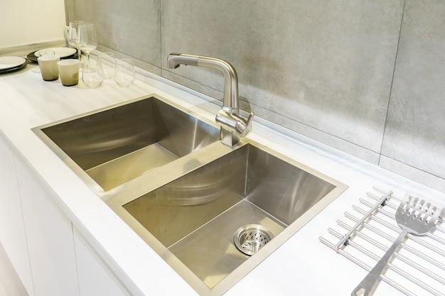 Nierdzewny zlew kuchenny i woda z kranu w kuchni. wbudowane urządzenia. urządzenie kuchenne.