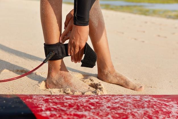 Nierozpoznana bosa kobieta ma naprawioną nogawkę, stoi na piasku obok deski surfingowej
