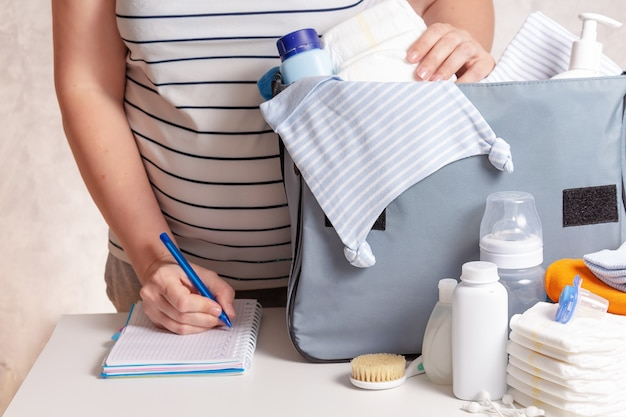 Nierozpoznana ciężarna kaukaska kobieta w t-shircie w paski pakująca dużą niebieską torbę na pieluchy do szpitala położniczego. pieluchy, pieluchy, czapka, butelka i inne niezbędne rzeczy dla noworodka.