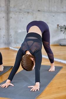 Nierozpoznana kobieta ćwiczy na sali.
