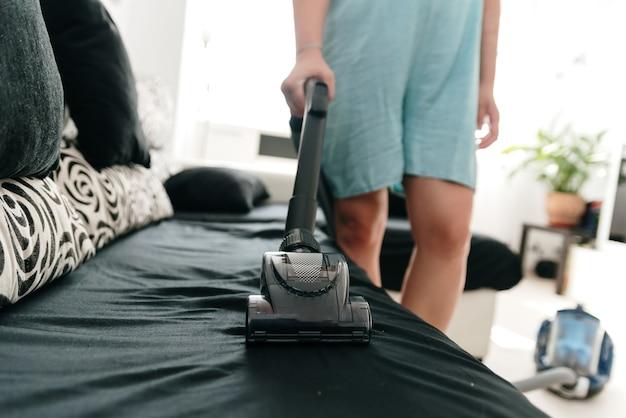 Nierozpoznana kobieta czyści sofę odkurzaczem.