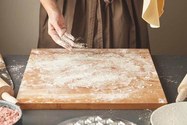 Nierozpoznana kobieta posypuje białą mąkę na drewnianej desce, trzymając w powietrzu spłaszczone ciasto na makaron lub pierogi. gotowanie ravioli krok po kroku