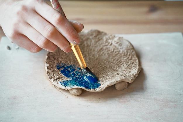 Nierozpoznana kobieta robi wzorowi na ceramicznym talerzu, wręcza zakończenie, skupia się na dłoniach