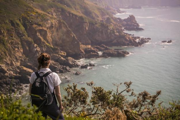 Nierozpoznana kobieta stojąca na krawędzi klifu i podziwiająca guernsey na wyspach normandzkich