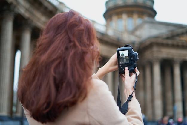 Nierozpoznana osoba stojąca z odwróconymi plecami i fotografująca zabytki
