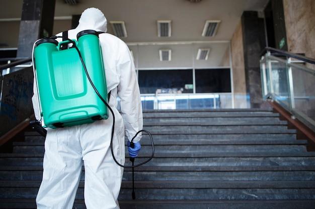 Nierozpoznana osoba w białym kombinezonie chroniącym przed chemikaliami ze zbiornikiem dezynfekującym korytarz publiczny, aby powstrzymać rozprzestrzenianie wysoce zaraźliwego wirusa koronowego