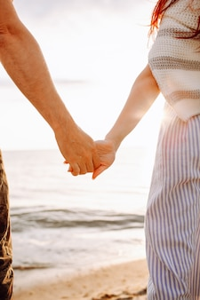 Nierozpoznana para trzyma się za ręce wzdłuż pustego piasku plaży oceanu o zachodzie słońca. widok z tyłu.