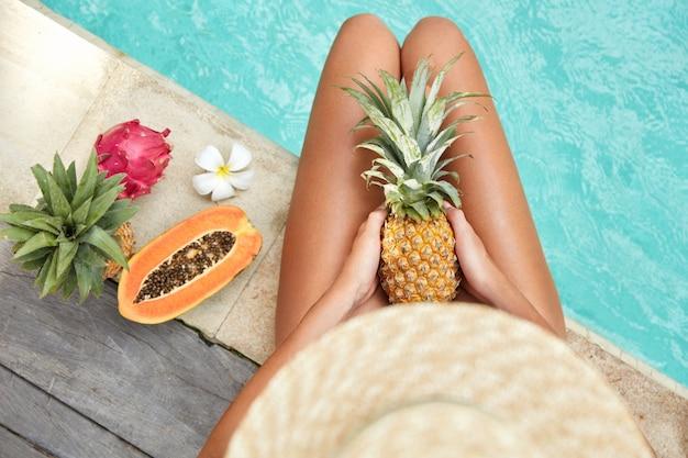Nierozpoznana turystka odpoczywa samotnie przy letnim basenie z wodą, trzyma ananas w otoczeniu owoców tropikalnych, cieszy się dobrym wypoczynkiem. opalona, szczupła kobieta je soczyste owoce, aby zachować zdrowie i kondycję