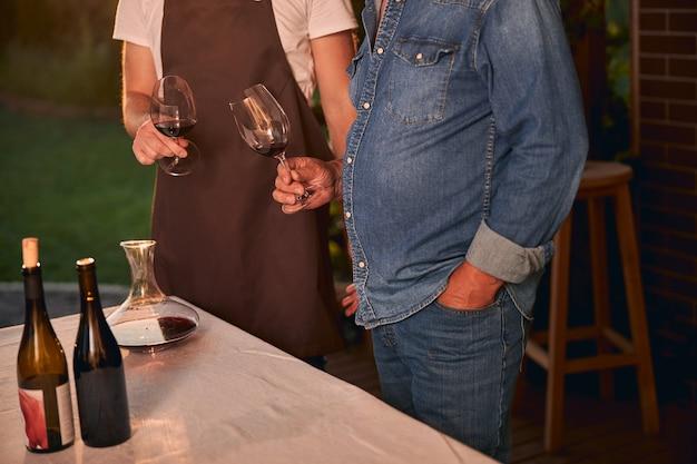 Nierozpoznani mężczyźni stojący na tarasie o zachodzie słońca z kieliszkami czerwonego wina w rękach. karafka i butelki na stole