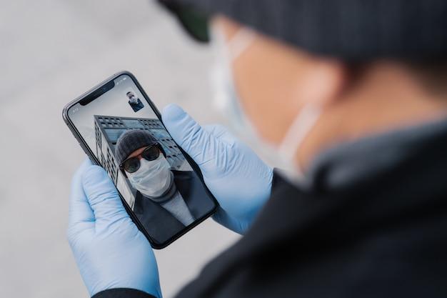 Nierozpoznany mężczyzna ma rozmowę wideo na zewnątrz, trzyma telefon komórkowy w gumowych rękawicach ochronnych, nosi maskę ochronną z powodu rozprzestrzeniania się epidemii koronawirusa, rozmawia z przyjacielem, omawia wiadomości