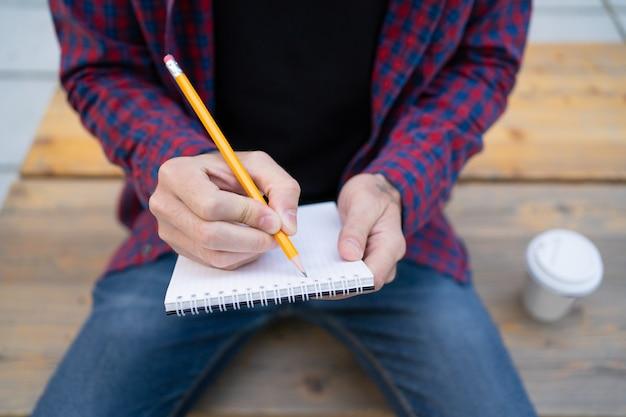 Nierozpoznany mężczyzna pisze w notatniku z ołówkiem