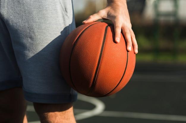 Nierozpoznany mężczyzna trzyma koszykówkę