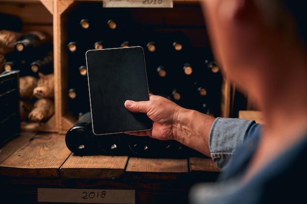 Nierozpoznany mężczyzna trzymający tablet przed półką winiarni z rzędem butelek