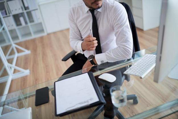 Nierozpoznany mężczyzna w formalnej koszuli i krawacie pracujący w biurze