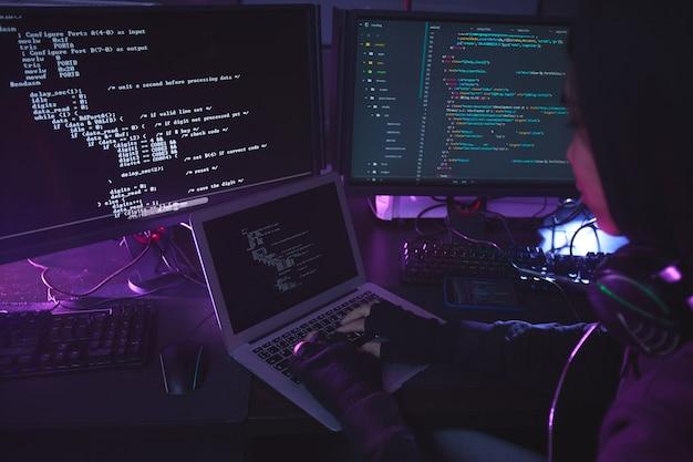 Nierozpoznany młody człowiek otoczony wieloma ekranami programującymi lub włamującymi się do zabezpieczeń w ciemnym pokoju, kopiuj przestrzeń