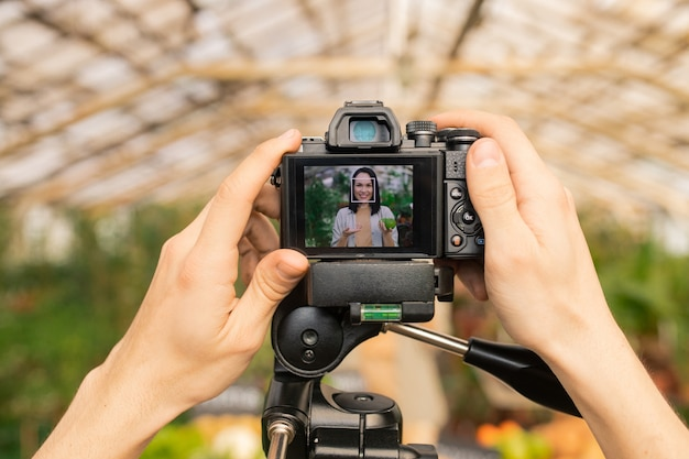 Nierozpoznany operator dostosowujący kamerę do kręcenia recenzji wideo azjatyckiego blogera zdrowej żywności w szklarni