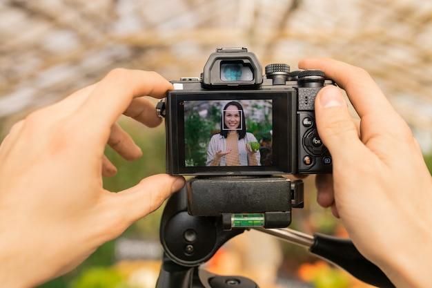 Nierozpoznany operator kamery kręci film z azjatyckim rolnikiem opowiadającym o zdrowej żywności ekologicznej na blogu