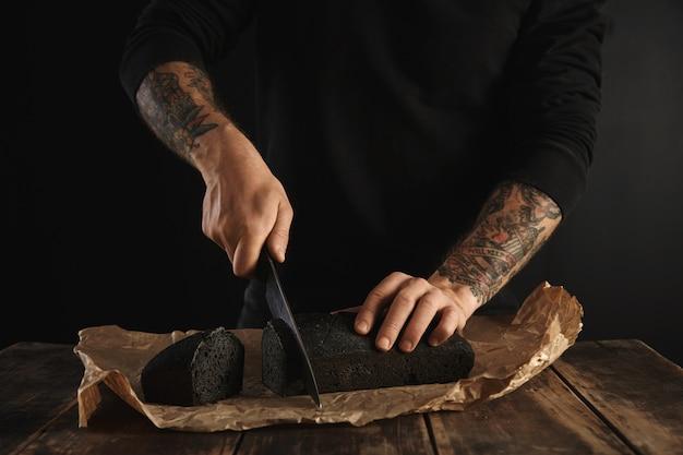Nierozpoznany piekarz z wytatuowanymi rękami pokroił świeżo upieczony domowy chleb na węgiel drzewny z dużym głównym nożem na plasterkach na papierze rzemieślniczym na drewnianym rustykalnym stole