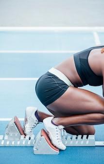 Nierozpoznawalna afro sportsmenka w stroju sportowym rozpoczynająca wyścig z pozycji przykucniętej na blokach startowych