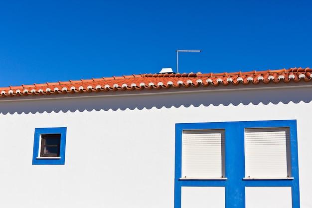 Nierozpoznawalna część domu mieszkalnego w algarve, portugalia. jasne błękitne niebo jako tło