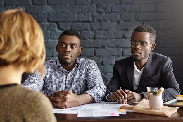 Nierozpoznawalna kandydatka o krótkich włosach przeprowadza rozmowę kwalifikacyjną z dwoma atrakcyjnymi biznesmenami