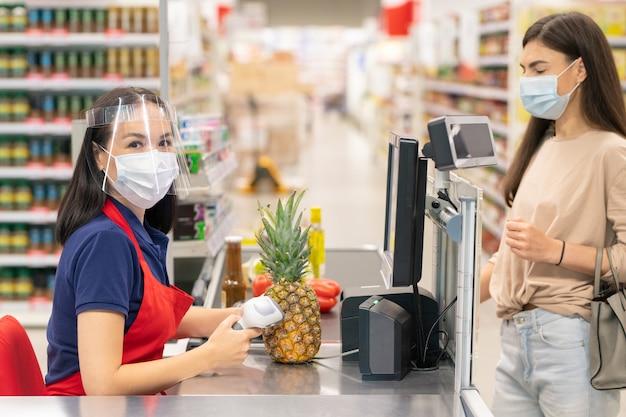 Nierozpoznawalna kasjerka w supermarkecie używająca komputera do wyszukiwania ceny sosu, którą zamierza kupić jej klient