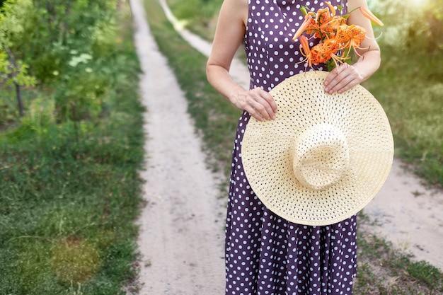 Nierozpoznawalna kaukaska kobieta w słonecznym wiklinowym kapeluszu w dłoniach stoi na wiejskiej drodze