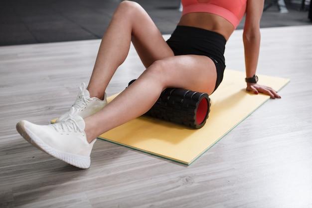 Nierozpoznawalna kobieta fitness lexaing obolałe ścięgna podkolanowe na piankowym wałku w studiu sportowym