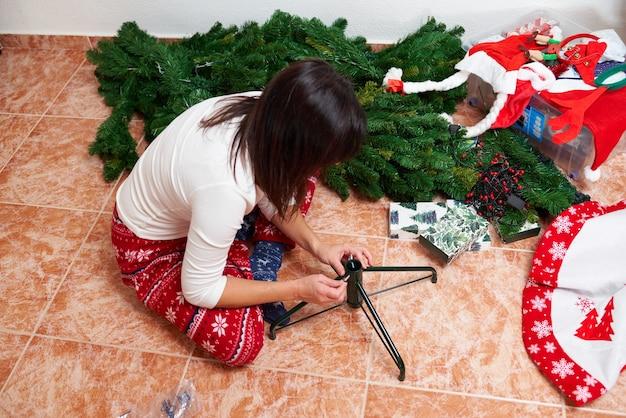 Nierozpoznawalna kobieta montująca choinkę