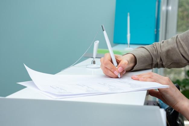Nierozpoznawalna kobieta podpisuje dokument, z bliska