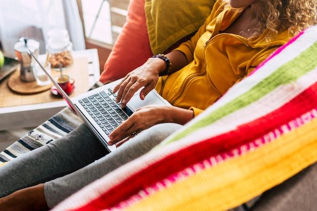 Nierozpoznawalna kobieta pracuje w domu z laptopem siedząc na kanapie