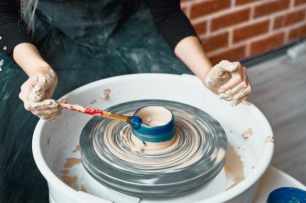 Nierozpoznawalna kobieta robi ceramiki na kole, maluje błękit. koncepcja dla niezależnych kobiet