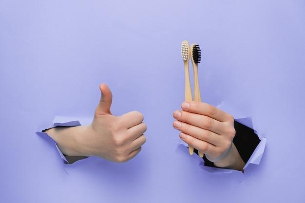 Nierozpoznawalna kobieta robi gest kciukiem do góry, pokazuje bambusowe szczoteczki do zębów eco, gesty przez podarte papierowe fioletowe tło.