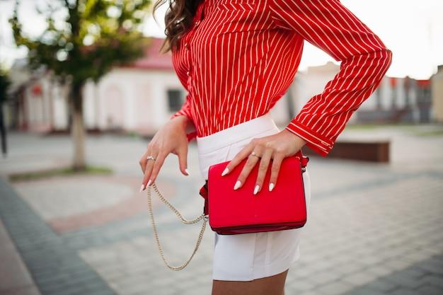 Nierozpoznawalna kobieta w czerwonej koszuli w paski i mini szortach z czerwoną torebką na ulicy.