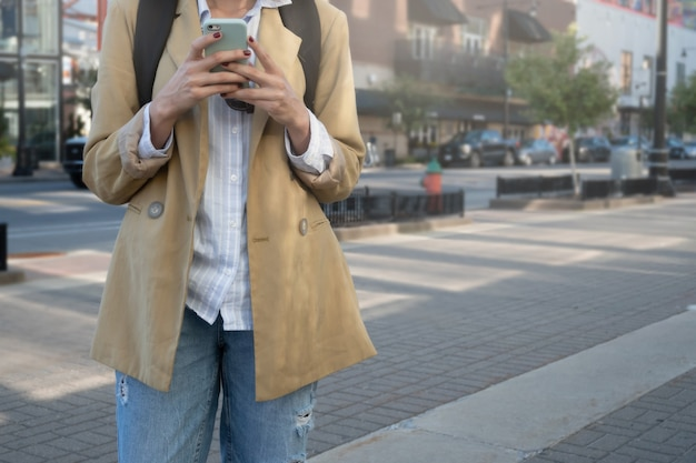 Nierozpoznawalna kobieta w kurtce i plecaku pisze wiadomość z telefonem komórkowym w mieście, z miejscem na kopię