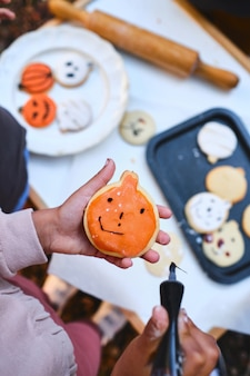 Nierozpoznawalna mała dziewczynka dekorująca domowe ciasteczka na halloween
