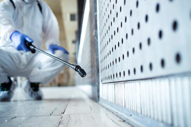Nierozpoznawalna osoba w białym kombinezonie chroniącym przed chemikaliami przeprowadzająca dezynfekcję miejsc publicznych, aby powstrzymać rozprzestrzenianie wysoce zaraźliwego wirusa koronowego
