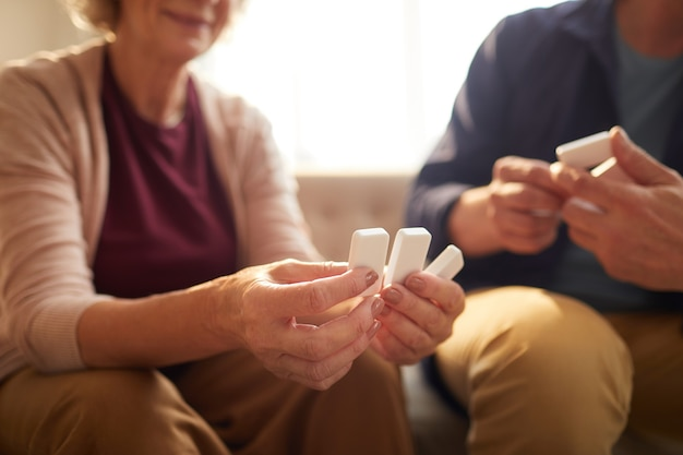 Nierozpoznawalna para seniorów trzymająca klocki domina podczas grania w gry planszowe w domu