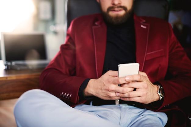 Nierozpoznawalny biznesmen używający swojego telefonu komórkowego