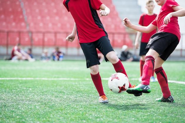 Nierozpoznawalny chłopiec kopie piłkę podczas treningu piłki nożnej