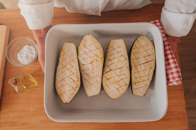 Nierozpoznawalny kucharz w domu gotuje tacę z bakłażanami, aby zabrać je do piekarnika