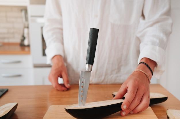 Nierozpoznawalny kucharz w domu robi cięcia w bakłażanie, aby był bardziej miękki