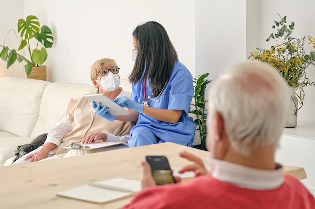 Nierozpoznawalny lekarz z tabletem rozmawiający z starszym pacjentem w domu
