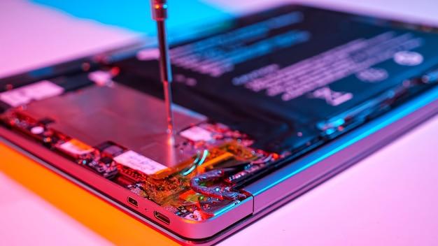 Nierozpoznawalny mężczyzna demontuje laptopa śrubokrętem w wyciszonym czerwonym i niebieskim świetle